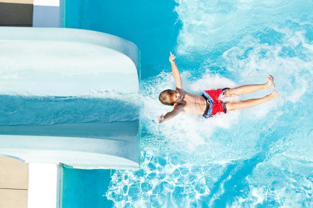Boy Exiting Water Slide into Swimming Pool